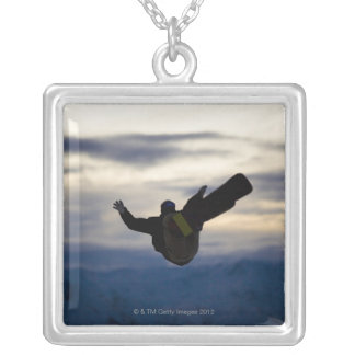 A male snowboarder does a back flip while riding silver plated necklace
