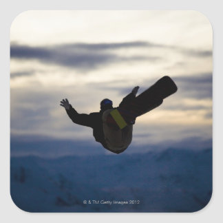 A male snowboarder does a back flip while riding square sticker