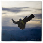A male snowboarder does a back flip while riding ceramic tile