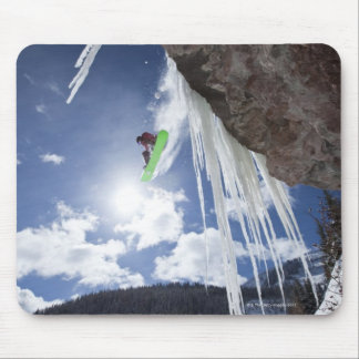 A male snowboarder jumps off an ice waterfall mouse pad