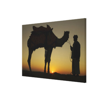 a man and his camel Silhouetted at sunset on the Canvas Print