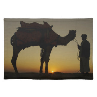 a man and his camel Silhouetted at sunset on the Place Mats
