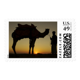 a man and his camel Silhouetted at sunset on the Postage Stamps