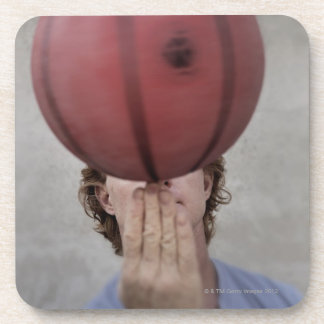 A man spinning a basketball ball on his finger beverage coaster