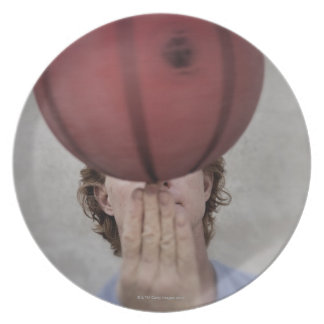 A man spinning a basketball ball on his finger melamine plate