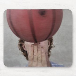 A man spinning a basketball ball on his finger mouse pad