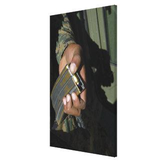 A Marine loads blank ammunition rounds Canvas Print
