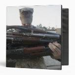 A marine readies 80 pounds of enemy rifles seiz vinyl binders