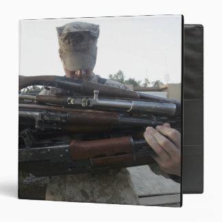 A marine readies 80 pounds of enemy rifles seiz vinyl binder