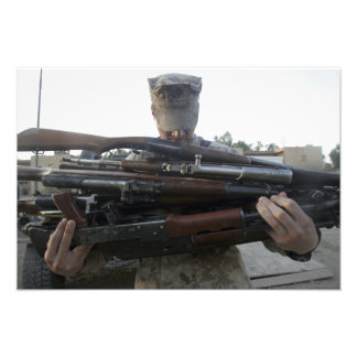 A marine readies 80 pounds of enemy rifles seiz photograph