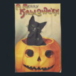 """A Merry Halloween, Vintage Black Cat in Pumpkin Towel<br><div class=""""desc"""">Vintage illustration Halloween holiday design featuring a cute black kitten. The happy cat is sitting in a jack-o-lantern pumpkin carved with a smile on his face. A Merry Halloween.</div>"""