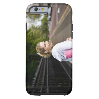 A mid adult woman carrying a yoga mat, walking tough iPhone 6 case