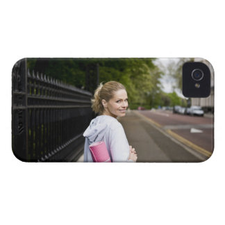 A mid adult woman carrying a yoga mat, walking iPhone 4 Case-Mate cases