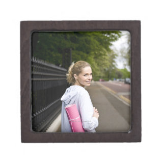 A mid adult woman carrying a yoga mat, walking gift box