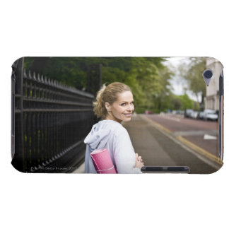 A mid adult woman carrying a yoga mat, walking iPod touch cover