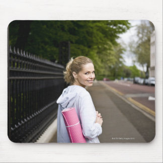 A mid adult woman carrying a yoga mat, walking mouse pad