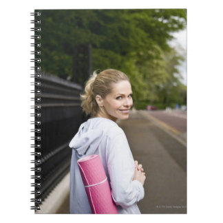 A mid adult woman carrying a yoga mat, walking spiral note books