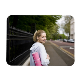 A mid adult woman carrying a yoga mat, walking rectangle magnet