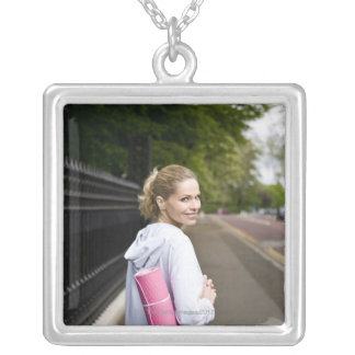 A mid adult woman carrying a yoga mat, walking silver plated necklace