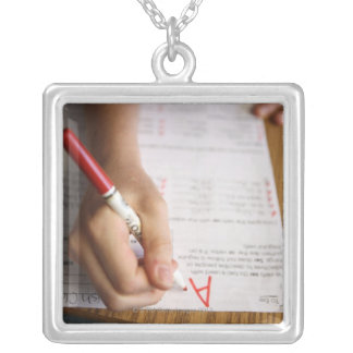 A middle school teacher puts a grade on a personalized necklace