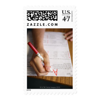 A middle school teacher puts a grade on a postage