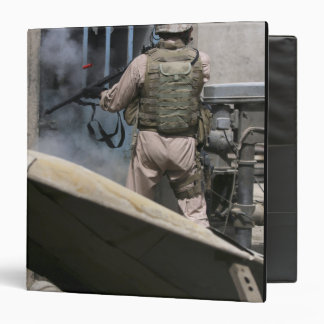 A military policeman uses a breaching round 3 ring binder