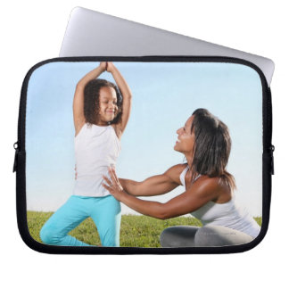 A mom helps her five-year-old girl with a yoga computer sleeves