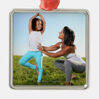 A mom helps her five-year-old girl with a yoga metal ornament