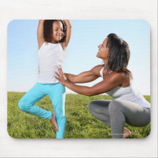 A mom helps her five-year-old girl with a yoga mousepad