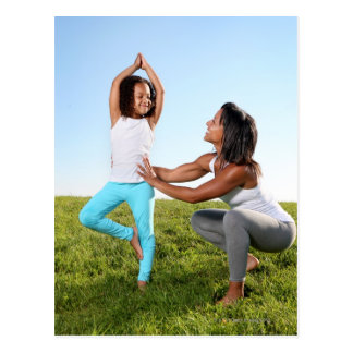 A mom helps her five-year-old girl with a yoga postcard