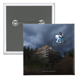 A mountain biker jumps off a log cabin in Idaho. 2 Inch Square Button