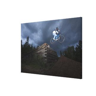 A mountain biker jumps off a log cabin in Idaho. Canvas Print