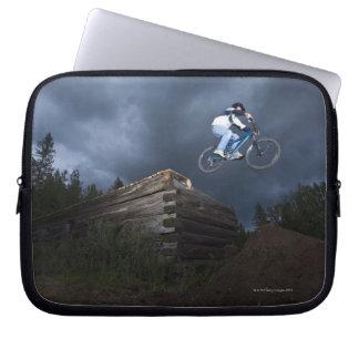 A mountain biker jumps off a log cabin in Idaho. Laptop Sleeve