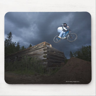 A mountain biker jumps off a log cabin in Idaho. Mouse Pad