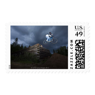 A mountain biker jumps off a log cabin in Idaho. Stamp