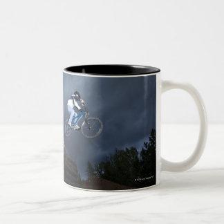 A mountain biker jumps off a log cabin in Idaho. Two-Tone Coffee Mug