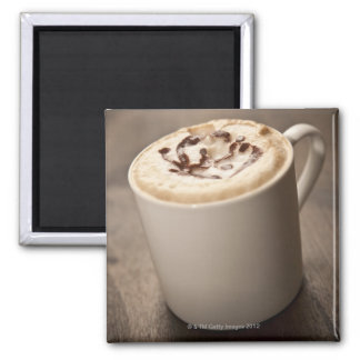 A mug of Cappuccino coffee topped with melted 2 Inch Square Magnet