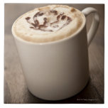 A mug of Cappuccino coffee topped with melted Ceramic Tile