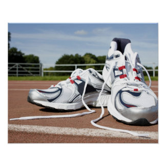 A pair of new white running trainers are placed poster