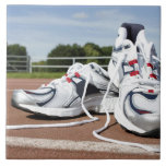 A pair of new white running trainers are placed ceramic tiles