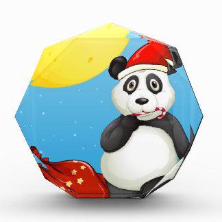 A panda wearing Santa's hat while eating a cane lo Acrylic Award