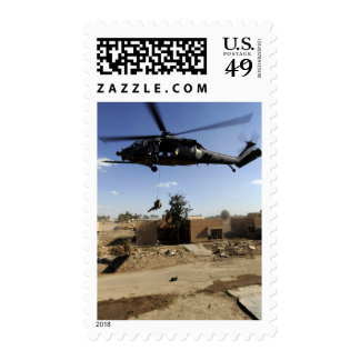 A pararescueman rappels from an HH-60 2 Stamps