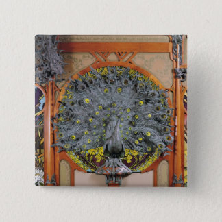 A peacock from the central panel of a mural button