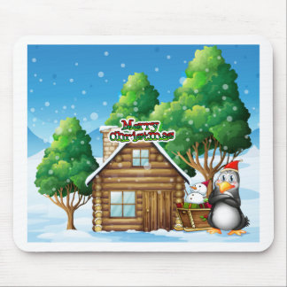 A penguin and a snowman beside the wooden house mouse pad