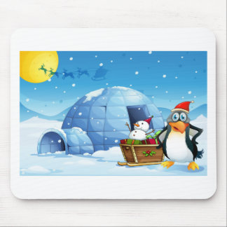 A penguin and the sleigh with a snowman near the i mouse pad