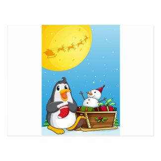 A penguin near the sleigh with a snowman postcard