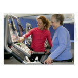 A personal trainer helps a senior woman on a card