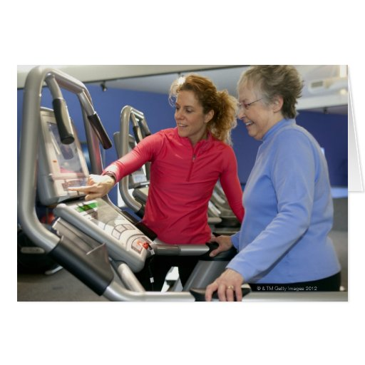 A personal trainer helps a senior woman on a greeting card