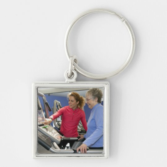 A personal trainer helps a senior woman on a keychain