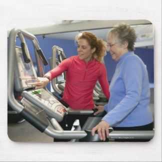 A personal trainer helps a senior woman on a mouse pad